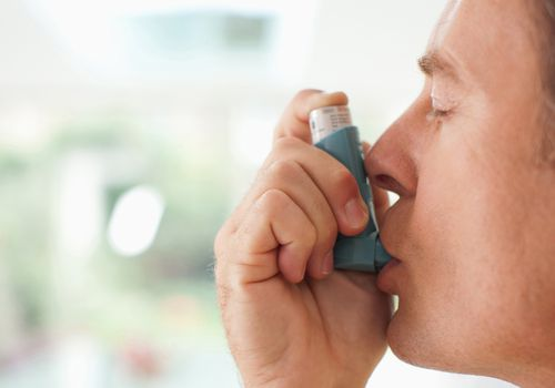 A man with asthma using his inhaler