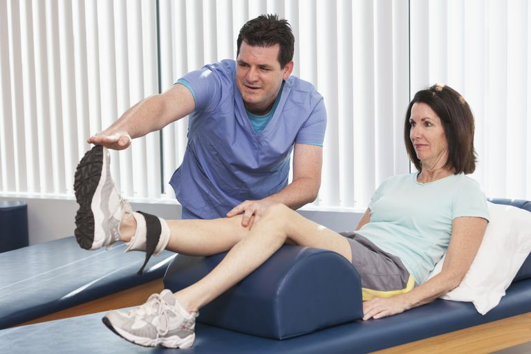 physical therapist helping woman with knee rehab