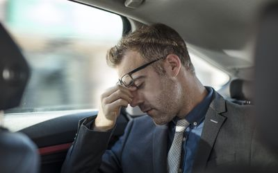 Businessman sitting in the back of a car rubbing his eyes