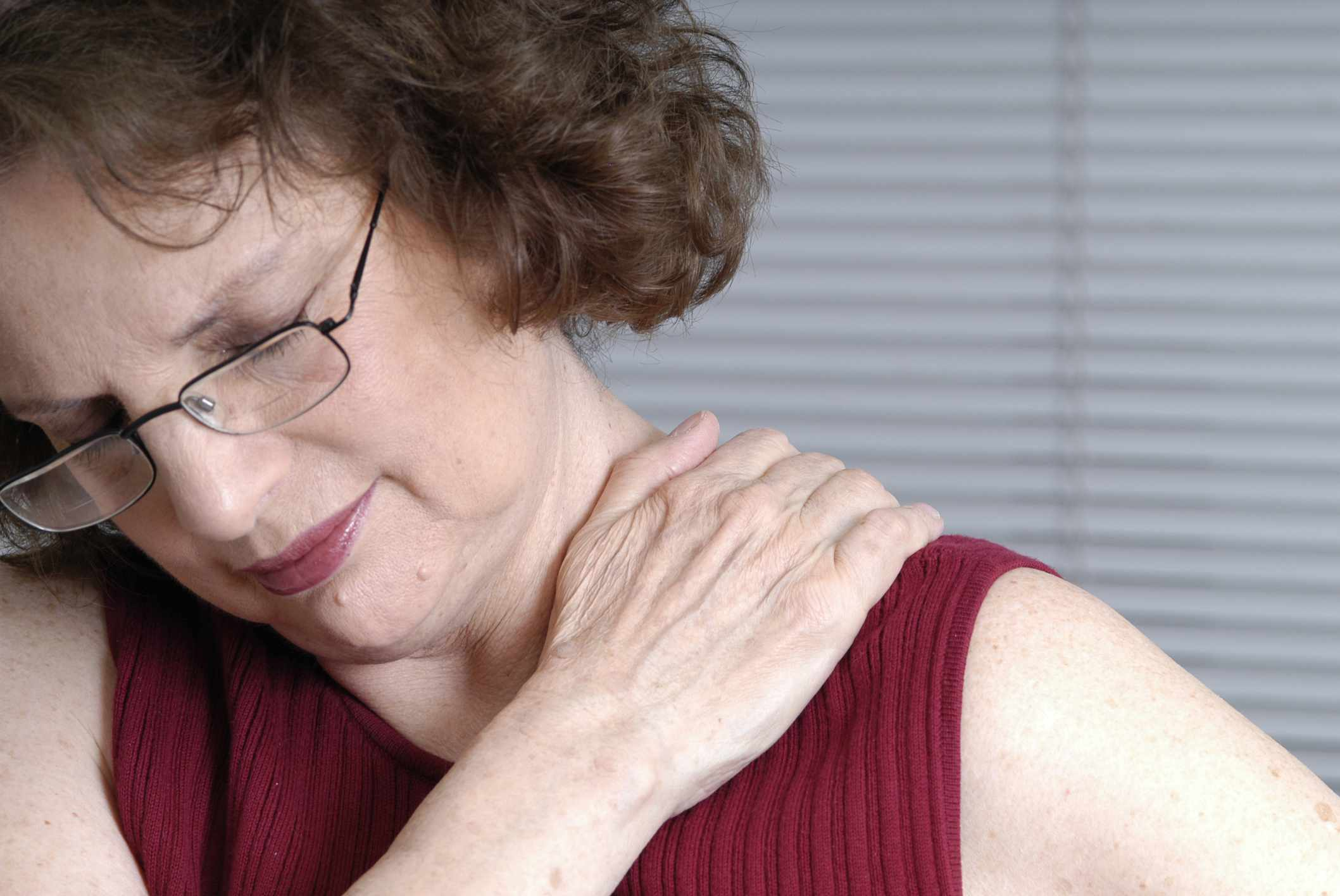 A woman clutching her shoulder from muscle strain
