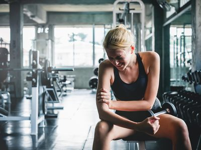 A woman in the gym with an injured shoulder