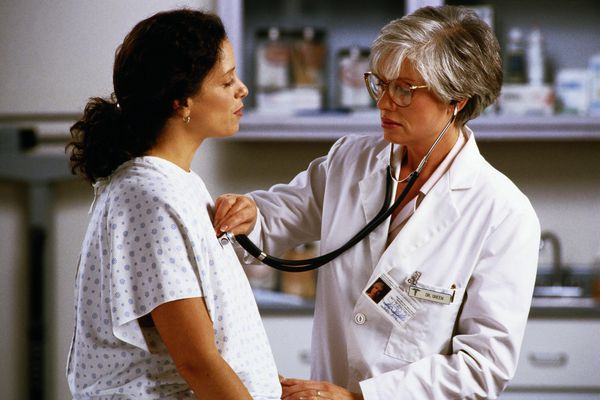 Mature female doctor examining female patient with stethoscope