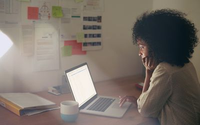 Woman looking at her laptop at a desk
