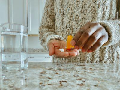 woman pours pills into hand from prescription bottle