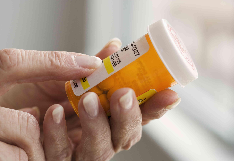 Hands holding a pill bottle