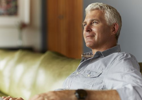 man smiling and thinking on couch