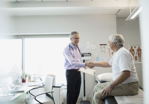 Doctor shaking hands with a senior man in an examination room