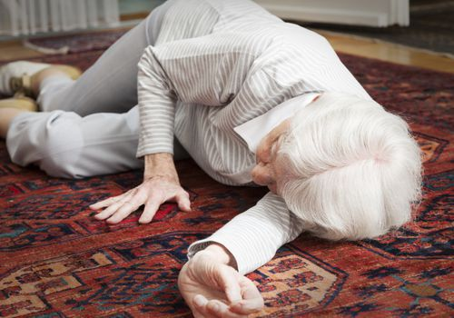 An older woman who has fallen on the ground