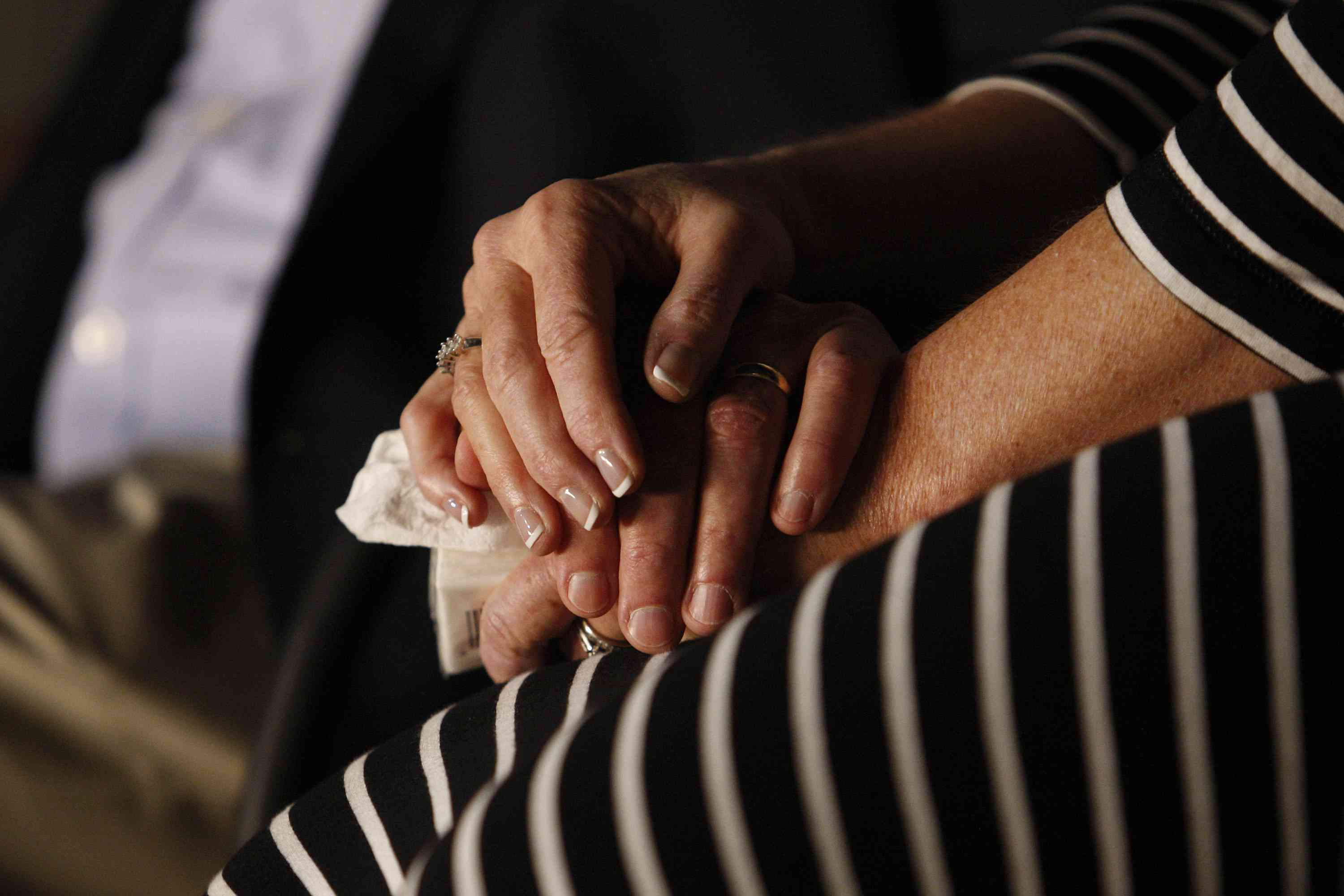 Close-up hands of grieving woman holding hand of friend