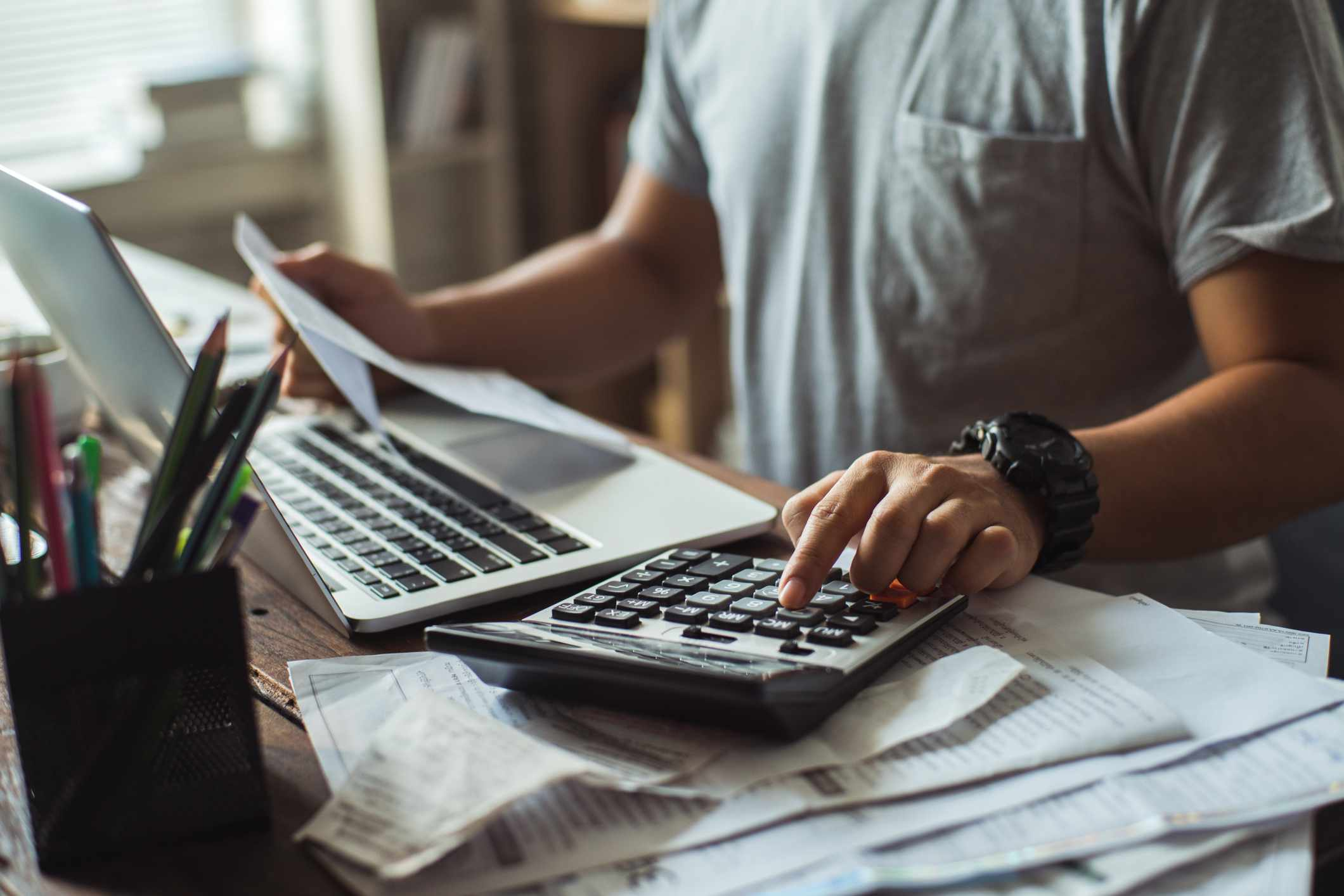Man calculating bills on his desk