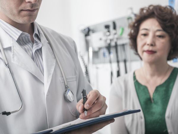 Doctor writing on medical chart with patient in the background