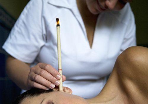 Woman lying down having ear candling
