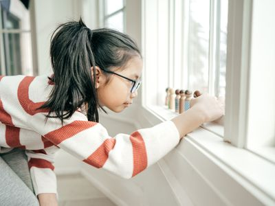 Girl playing with wooden figures on windowsill