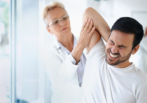 main with shoulder blade pain being evaluated by doctor
