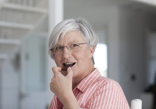 mature woman eating chocolate