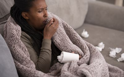 Sick woman with her hand over her mouth coughing, sitting wrapped with a warm blanket on the sofa at home. Female with cold or allergies.