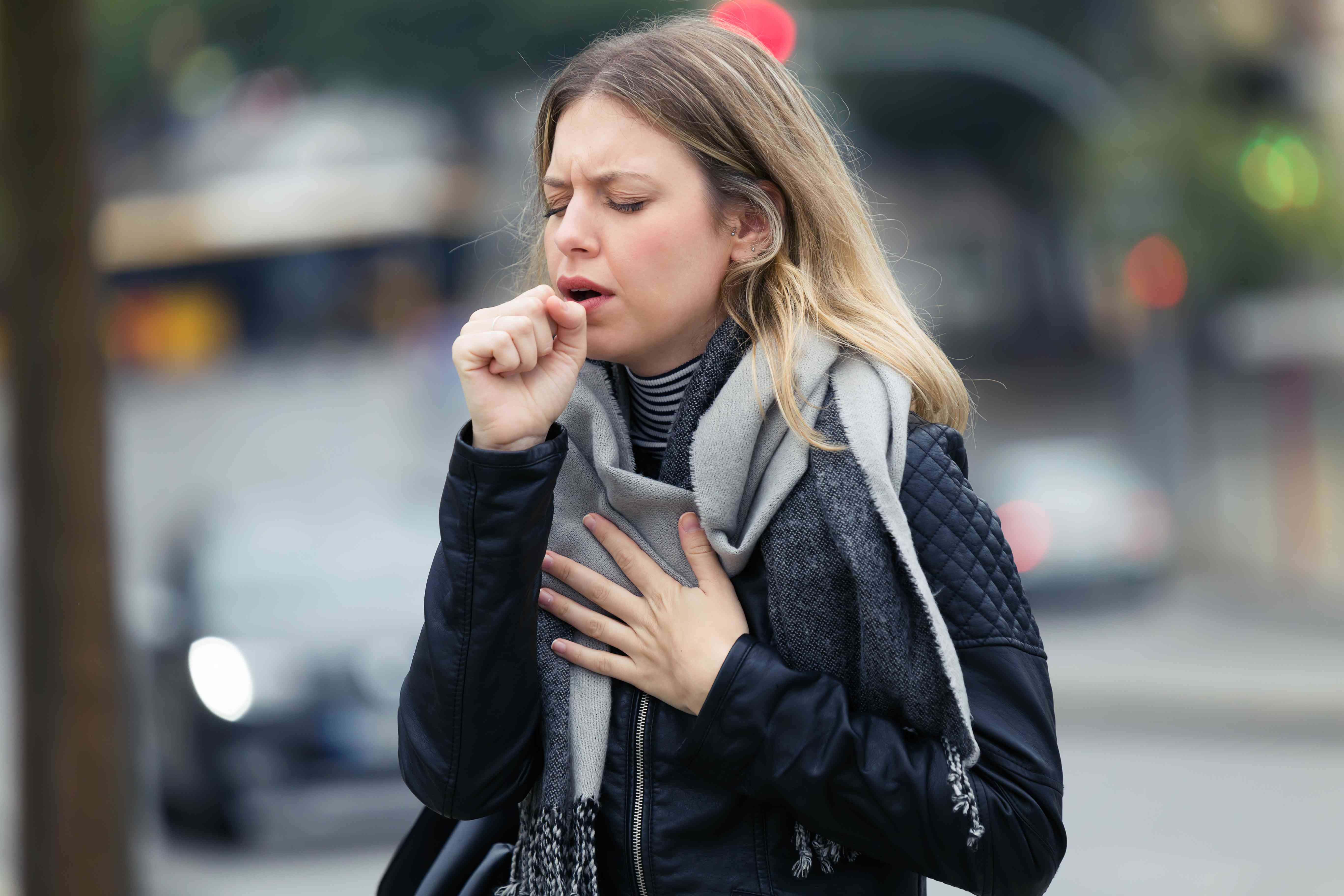 Illness young woman coughing in the street.