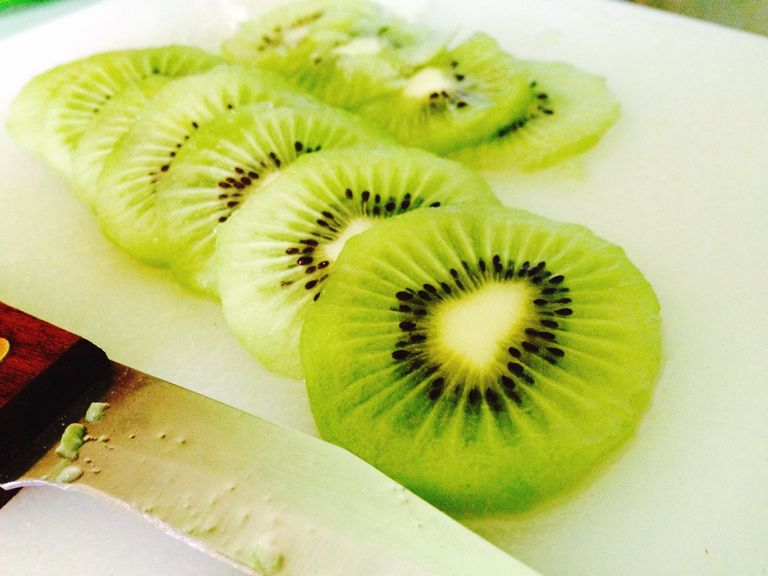 Close-Up Of Sliced Kiwi By Knife On Plate