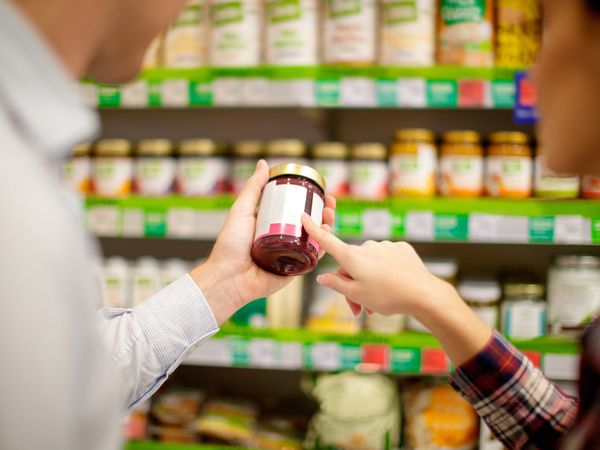 Couple choosing jar of jam
