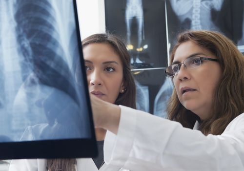 Hispanic doctors examining x-ray of chest