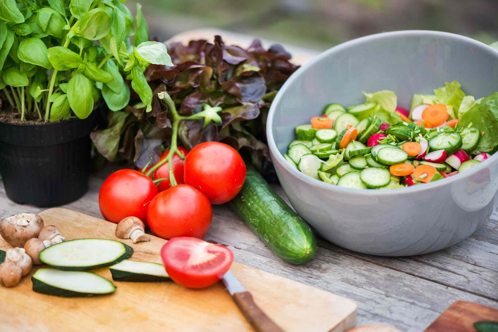 vegetables on cutting board with bowl of salad
