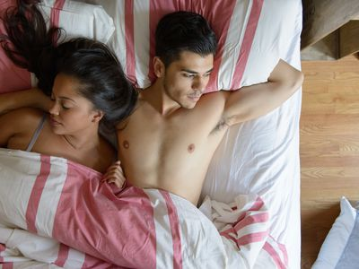 A man and woman laying in bed together