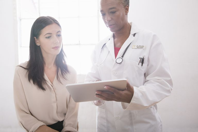 Woman and female doctor looking at a digital tablet