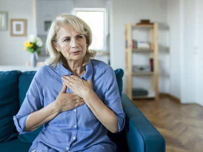 Woman grasping her chest sitting on a couch