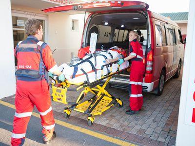 Paramedics lifting patient from ambulance