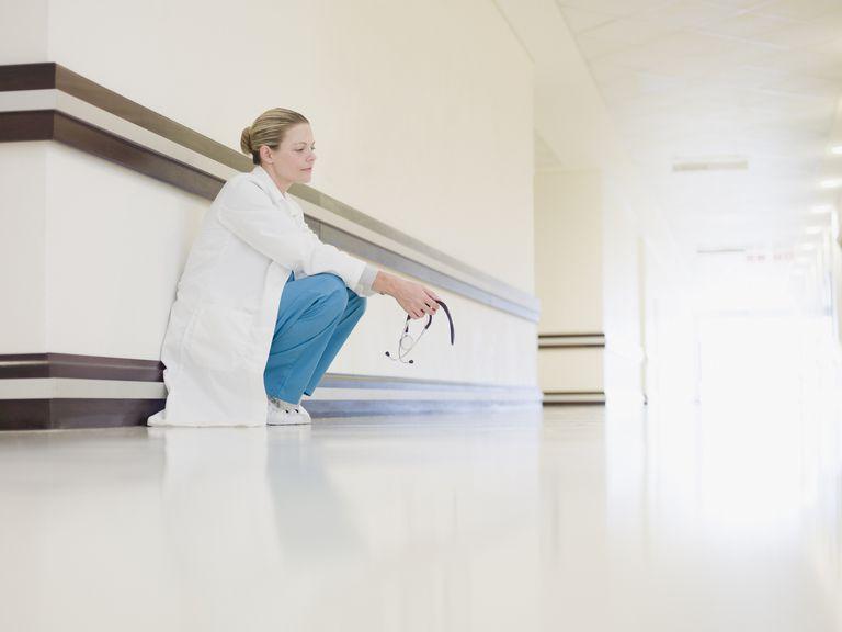 upset nurse crouching in hallway