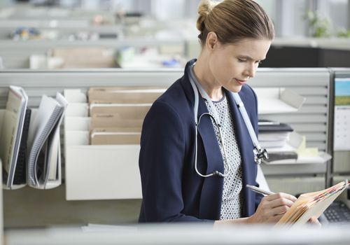 Female doctor writing notes.