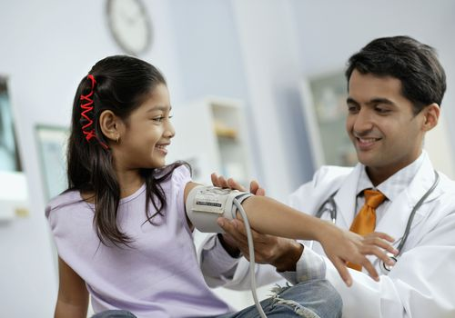 Doctor taking girl's blood pressure, both smiling