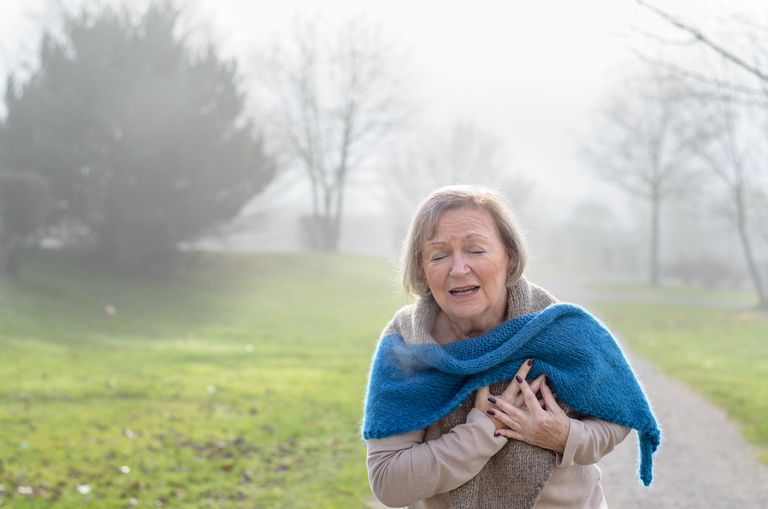 Senior Woman Suffering From Chest Pain While Standing On Field During Foggy Winter