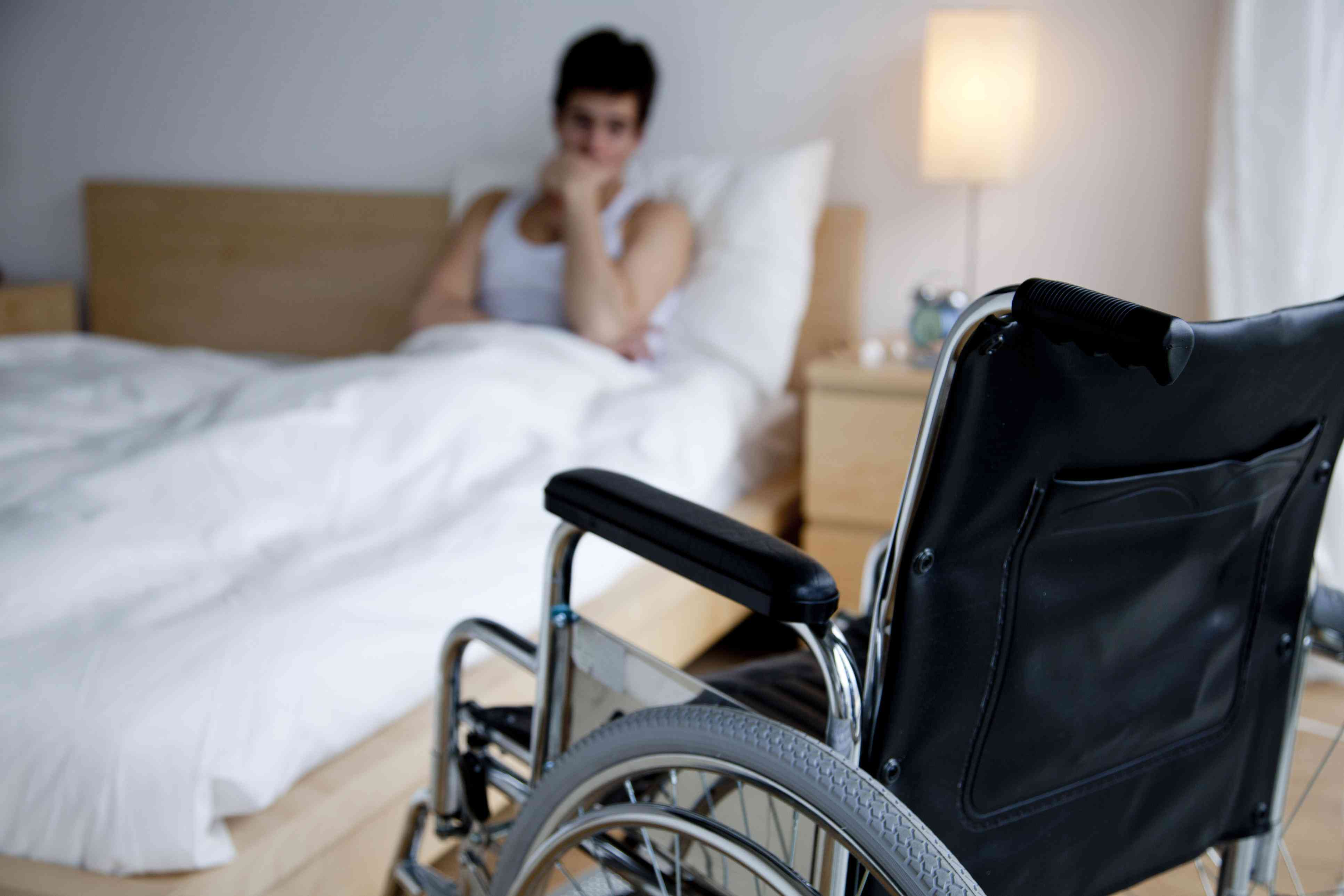 Disabled man in bed, out of reach of wheelchair