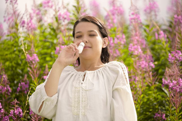 Woman using a nasal spray outside