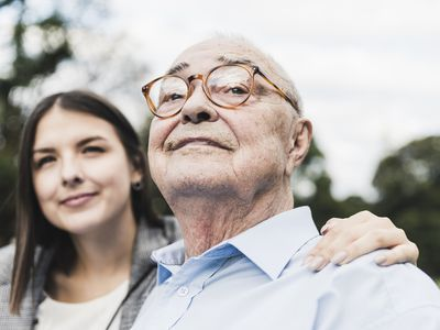 Older man with glasses comforted by his relative