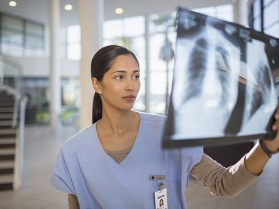 Nurse examining a chest x-ray with a shadow on the lung