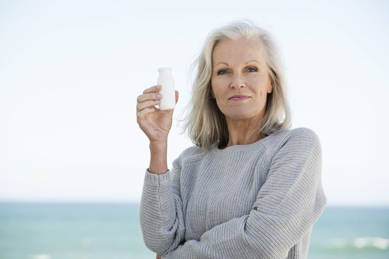 Woman holding a probiotic drink.
