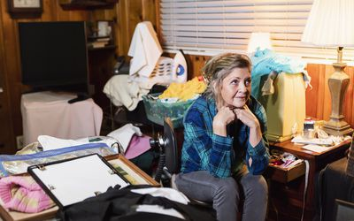 A senior woman in her 60s at home, sitting in a messy, cluttered room, looking away with a serious expression.
