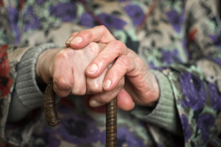 Close-up of an old wrinkled hand holding a cane.