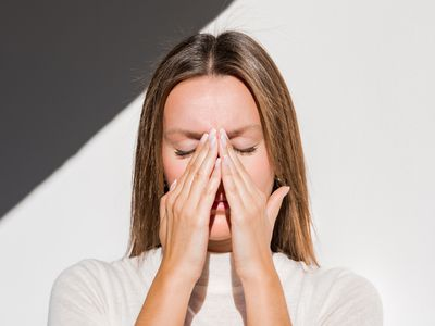 White woman holding her nose, her eyes are closed as though she's in pain. She's wearing a cream-colored shirt and the white wall behind her has a bit of shadow creeping in the upper left hand side of the frame.