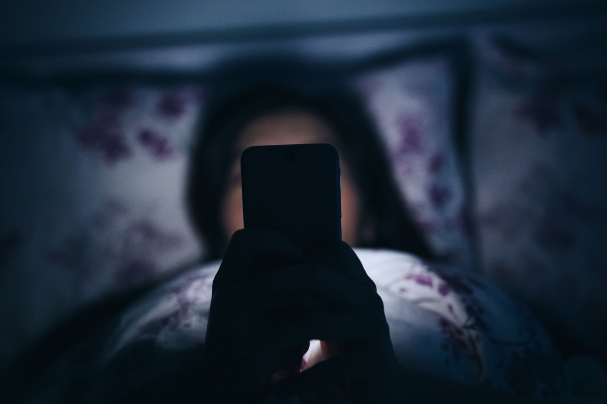 A woman texting on her bed at night