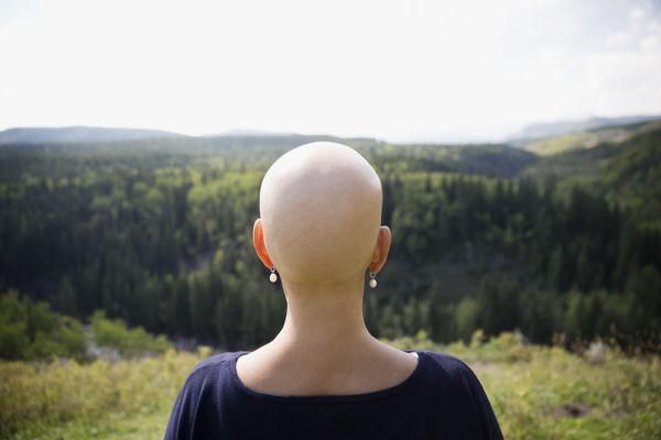 Female cancer survivor with shaved head looking at remote rural view