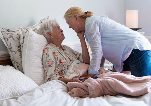 A senior woman in her bed embracing her daughter with emotion