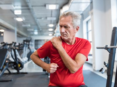 Senior man suffering from shoulder pain at rehabilitation center