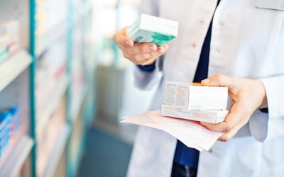 Pharmacist's hands taking medicines from shelf