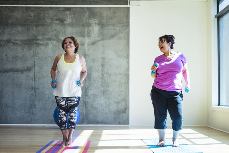 Two women smiling and working out