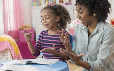 Mother helping daughter do math homework in playroom