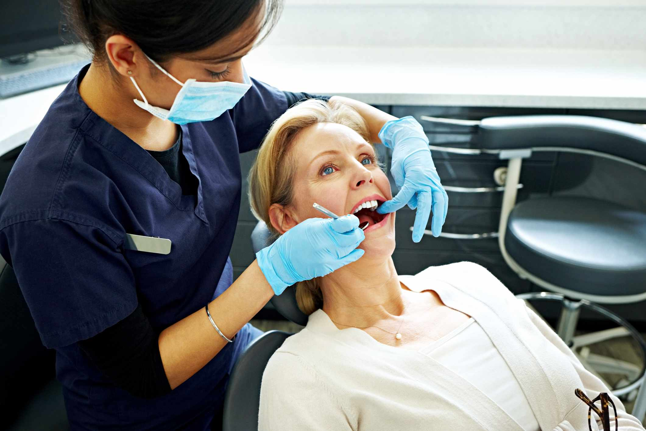 Woman having her teeth checked by dentist Portrait of mature woman having her teeth checked by dentist at dental clinic