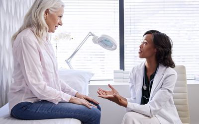 Woman at doctor speaking with woman doctor